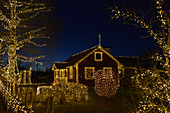 Beautiful Christmas decorations on house and garden at night, Långaryd, Halland, Sweden