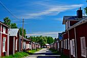 Eine Strasse mit traditionellen Holzhäusern in Gammelstad, Luleå, Norrbottens Län, Schweden