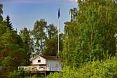Kleines Sommerhaus mit Veranda und Schwedenfahne im Wald, Näs bruk, Avesta, Dalarna, Schweden