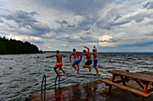Four men jump from a jetty into the lake, Siljansee, Sollerön, Dalarna, Sweden