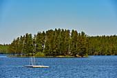 Eine kleine Badeplattform in einem See mit Insel umgeben von Wald, Provinz Örebro, Schweden