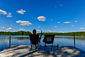 Relaxing with a beer on a jetty by the lake near Timansberg, Örebro Province, Sweden