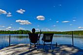 Entspannung bei einem Bier auf einem Steg am See bei Timansberg, Provinz Örebro, Schweden