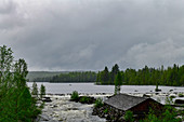 Lake and river with rapids and wooden hut in the forest, near Bräcke, Jämtland, Sweden