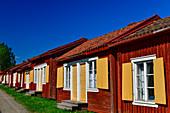 Row of red wooden huts with yellow shutters, Lövanger Kyrkstad, Västerbottens Län, Sweden