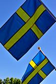Two Swedish flags against a blue sky, Bjuröklubb, Västerbottens Län, Sweden