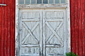 An old white wooden gate in a red boathouse, Bjuröklubb, Västerbottens Län, Sweden