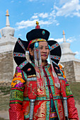 A Mongolian woman dressed in historic costume in front of the wall with stupas surrounding the Erdene Zuu monastery in Kharakhorum (Karakorum), a UNESCO World Heritage Site in Mongolia.