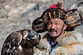 Portrait of the Kazakh Eagle hunter Dalaikhan and his Golden eagle near the city of Ulgii (Ölgii) in the Bayan-Ulgii Province in western Mongolia.