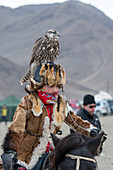 A teenage boy with a saker falcon (Falco cherrug) on his head at the Golden Eagle Festival near the city of Ulgii (Ölgii) in the Bayan-Ulgii Province in western Mongolia.