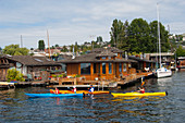 People kayaking along the houseboats on Lake Union in Seattle, Washington State, USA.