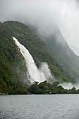 Heavy rain creating waterfalls in Milford Sound, Fjordland National Park on the South Island in New Zealand.