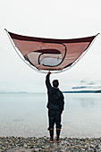 Man holding camping tent over head, standing on rocky beach,an inlet on the Alaska coastline.