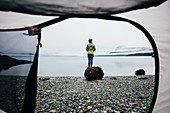 View through camping tent doorway of woman standing on beach,an inlet on the Alaska coastline.