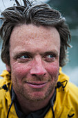 Portrait of smiling middle aged man in a yellow jacket outdoors