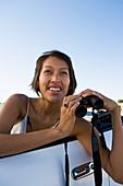 Native American woman in sun dress driving a white convertible sports car looking through binoculars