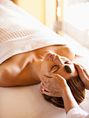 Woman lying on massage table receiving facial stone massage at a luxury spa in Napa Valley California