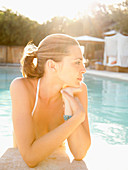 Beautiful contemplative woman in water looking off leaning on edge of swimming pool at a luxury California resort