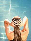 Rear view of woman in water with hands on head at a luxury resort in California