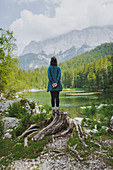 Germany, Bavaria, Eibsee, Young woman standing on stump by Frillensee?lake in Bavarian Alps