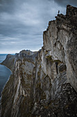 Norway, Senja, Man standing on the edge of steep cliff on top of Segla mountain