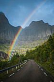 Norway, Lofoten Islands, Rainbow above empty road in mountain landscape