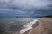 Baltic sea beach pier in Zinnowitz with cloudy skies and waves, Usedom, Mecklenburg-Western Pomerania, Germany