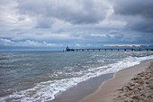 Baltic Sea beach with a view of the pier in Zinnowitz with cloudy skies and waves, Usedom, Mecklenburg-Western Pomerania, Germany