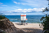 Rescue tower on the beach of Bansin with motor boat light swell cloudy sky, Usedom, Mecklenburg-Western Pomerania, Germany