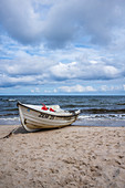 Fishing boat on the Baltic Sea beach with cloudy, dramatic sky and rough sea, Usedom, Mecklenburg-Western Pomerania, Germany