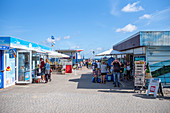 Access to the pier in Zinnowitz with a blue summer sky with people and shops, Usedom, Mecklenburg-Western Pomerania, Germany
