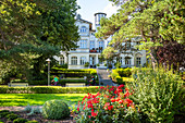 Green area in Zinnowitz with roses in front of an old villa and tourists, Usedom, Mecklenburg-Western Pomerania, Germany