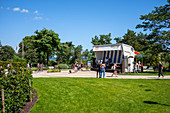 Promenade in Heringsdorf with an oversized beach chair, green spaces vacationers and tourists, Usedom, Mecklenburg-Western Pomerania, Germany