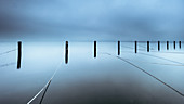 Foggy winter morning in abandoned marina, wooden posts in Lake Starnberg, Seeshaupt, Bavaria, Germany