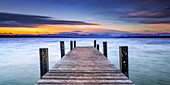 Jetty in sunrise on Lake Starnberg with mountain view, Bavaria, Germany