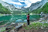 View over the small Gosau lake to the Dachstein and Dachstein glacier with woman in the foreground.