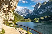 Großer Gosausee mit Kletterwänden und Weg im Vordergrund. Blick auf das Dachsteinmassiv, Salzkammergut, Oberösterreich, Österreich