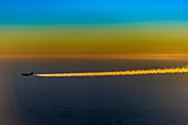 Airplane with contrails at dawn