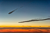 Airplanes with contrails just before sunrise