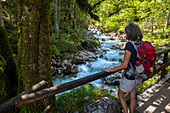 Hiking, woman at the Ramsauer Ache torrent, Berchtesgadener Land, Upper Bavaria, Germany