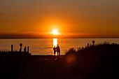 Paar am Ostseestrand von Großenbrode bei Sonnenuntergang, Schleswig-Holstein, Deutschland