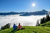 Mann und Frau sitzen auf Wiese und blicken auf Bergpanorama, Nebelmeer im Tal, Nebelhorn und Höfats im Hintergrund, am Himmelschrofen, Allgäuer Alpen, Allgäu, Bayern, Deutschland