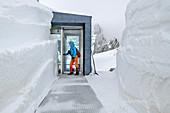 Woman enters the entrance area of a modern mountain hut, Seethalerhütte, Dachstein, Upper Austria, Austria through a snow tunnel