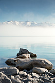 View of snow capped mountains on the horizon from Lake Pukaki in Canterbury, New Zealand.