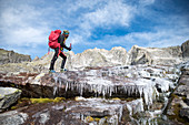 Hiker crossing a frozen creek along Sentiero Roma, Valle del Ferro, Val Masino, Valtellina, Sondrio province, Lombardy, Italy