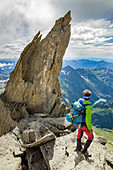 Hiker beside the rock pinnacle on eastern crest of Pizzo Andolla, between Loranco valley (Ossola) and Zwischbergental, (Switzerland)