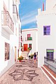 A woman walking on the moorish paved streets of Frigiliana, La Axarquia, Malaga province, Andalusia, Spain, Europe