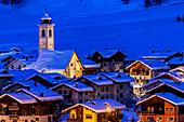 Church and houses illuminated during a winter twilight. Livigno, Valtellina, Lombardy, Italy, Europe.