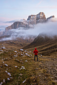Italy,Veneto,Belluno district,Selva di Cadore,hiker admires Mount Pelmo sticking out of the clouds