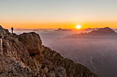 Italy, Veneto, Belluno district, Boite Valley,woman hiker at the top of Tofana di Mezzo admire the sunrise